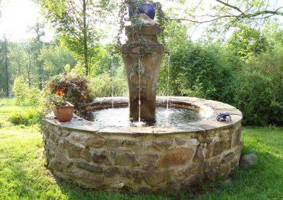handgearbeitete Brunnenstele aus Sandstein steht in runden Steinbecken