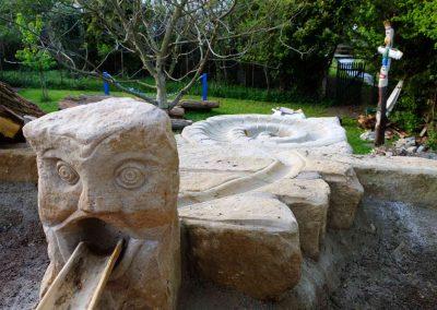 künstlerisch gestalteter Wasserspielplatz aus Naturstein mit Wasserspeier Wasserrinne und Wasserkaskade
