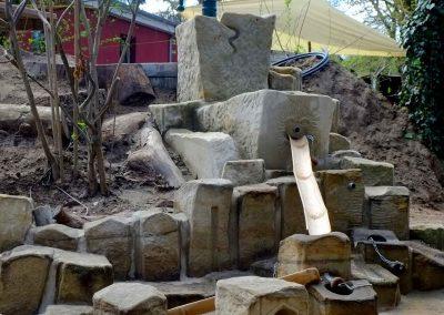 Naturnahe Spielanlage aus Sandstein zum spielen mit Wasser