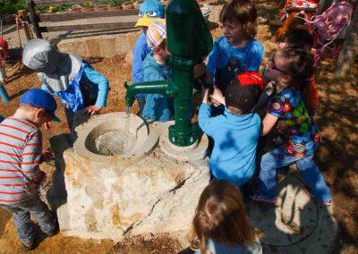 Kinder spielen mit Spielplatzpumpe