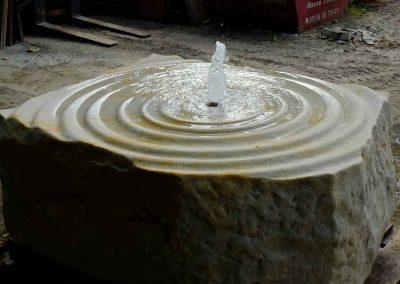 handbehauener Sandstein Brunnen - Quellstein, Wasser sprudelt über wellenförmige Steinfläche