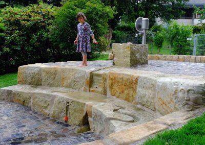 naturnaher Spielplatz für Wasser aus Naturstein mit Schwengelpumpe