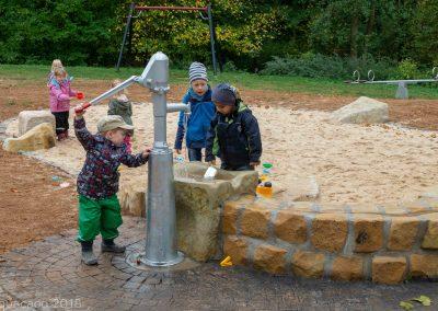 Kinder pumpen das Wasser in den Wasserlauf mit einer Schwengelpumpe von Richterspielgeräte