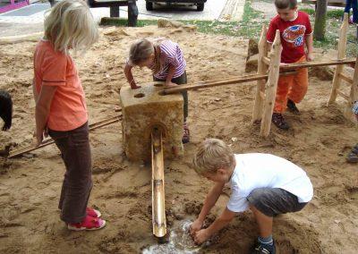 Die Kinder können Wasser mittels Stöpsel angestauen und mit Rinnen weiterleiten