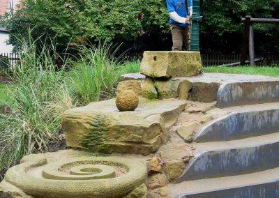 Wasserkaskade aus Sandstein mit Schwengelpumpe
