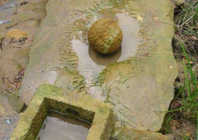Wasser fließt über große Steine in den Sandbereich