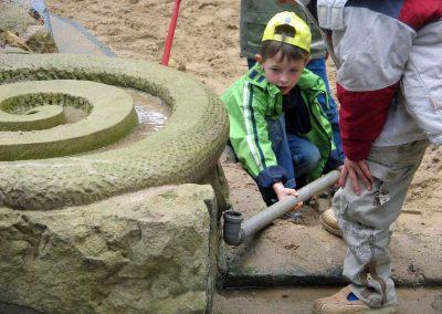 Kinder leiten Wasser an eine andere Stelle im Sandkasten