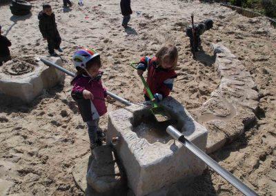 Kinder spielen in der neuen Wasserspielanlage der Kita Herne